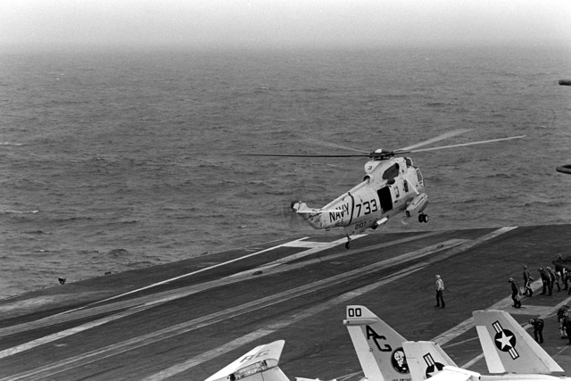 An SH-3 Sea King helicopter takes off from the flight deck during flight operations aboard the nuclear-powered aircraft carrier USS DWIGHT D. EISENHOWER (CVN-69). The SH-3 is assigned to Helicopter Squadron 5 (HS-5). Note: Second view in a series of five