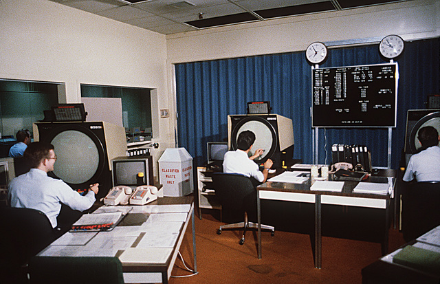 Interior view of the tactical operations room in the Pave Paws radar compound at the Cape Cod Missile Early Warning Station. From left to right are the systems directors console, missile warning console and space surveillance console