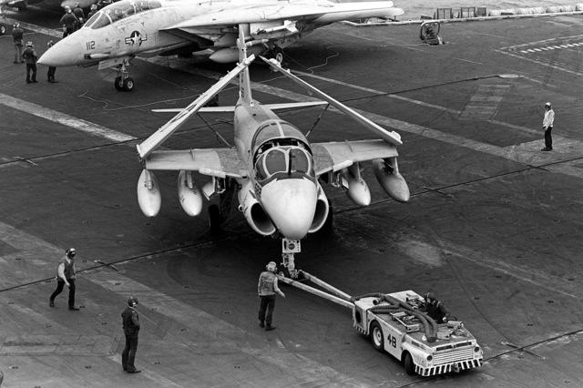 Members of the aircraft handling crew use an MD-3A tow tractor to move an A-6E Intruder aircraft to a parking spot during flight operations aboard the nuclear-powered aircraft carrier USS DWIGHT D. EISENHOWER (CVN-69). The A-6E is assigned to Medium Attack Squadron 65 (VA-65)