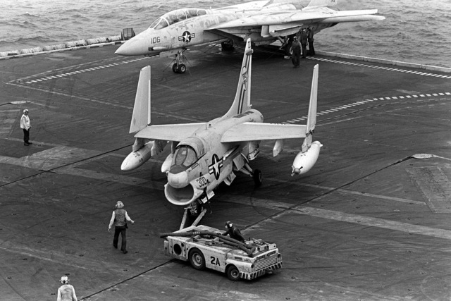 Members of the aircraft handling crew use an MD-3A tow tractor to move an A-7E Corsair aircraft to a parking spot during flight operations aboard the nuclear-powered aircraft carrier USS DWIGHT D. EISENHOWER (CVN-69). The A-7E is assigned to Light Attack Squadron 66 (VA-66)