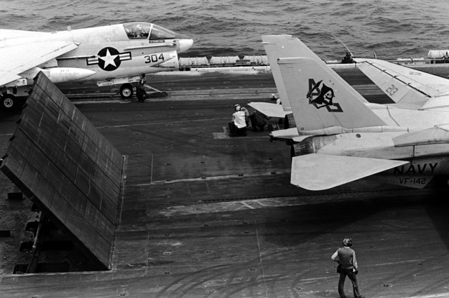Three blast deflector panels are raised behind an F-14 Tomcat aircraft from Fighter Squadron 142 (VF-142) during flight operations aboard the nuclear-powered aircraft carrier USS DWIGHT D. EISENHOWER (CVN-69). An A-7E Corsair II aircraft from Light Attack Squadron 66 (VA-66) is being attached to a steam catapult in the background. Second view in a series of eight