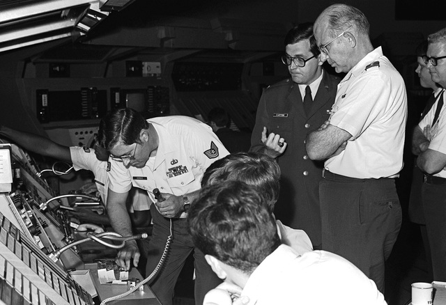 GEN Lew Allen Jr., chief of staff, U.S. Air Force, visits Tempelhof Central Airport. CPT Ronald Cartee, CATCO, briefs the general on console operations in the Berlin Air Route Traffic Control Center. The center is assigned to the 1956th Communications Squadron