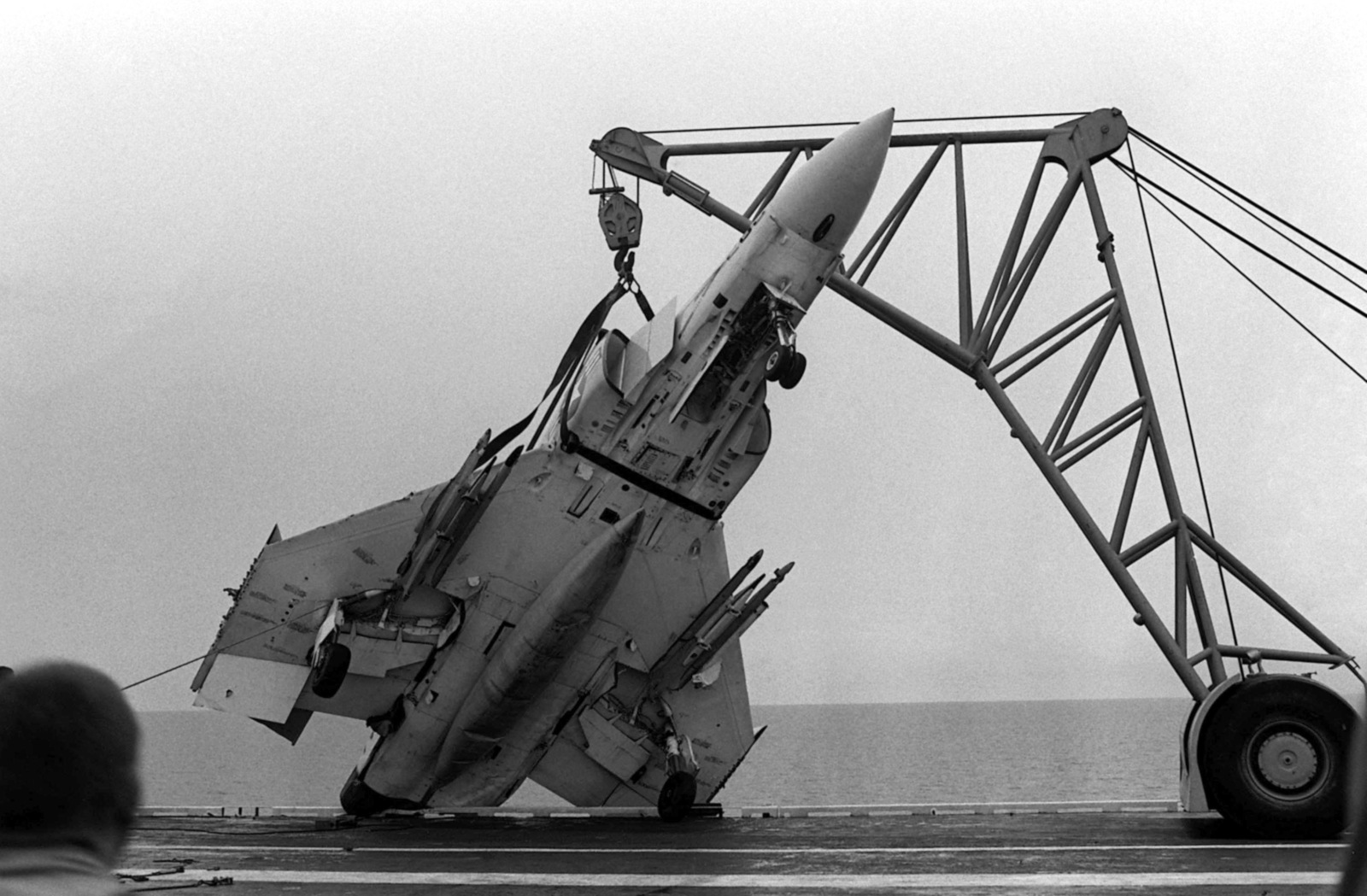 A crane is used to lift an F-4 Phantom II aircraft away from the port side deck edge of the aircraft carrier USS MIDWAY (CV 41). The F-4 was damaged when the MIDWAY collided with the Panamanian freighter CACTUS