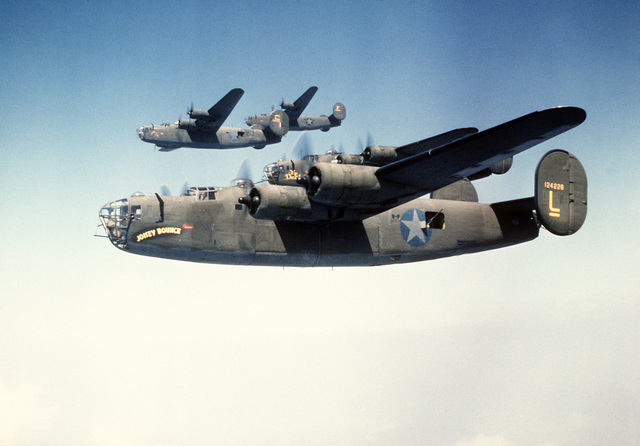 An air-to-air left side view of four B-24 Liberator aircraft in formation. The B-24 was built for World War II combat