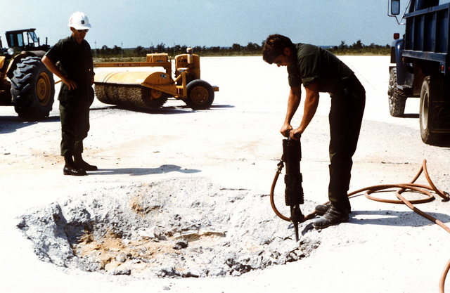 An airman clears a bomb blast crater on a runway, using a jackhammer, during a training exercise on rapid runway repair procedures