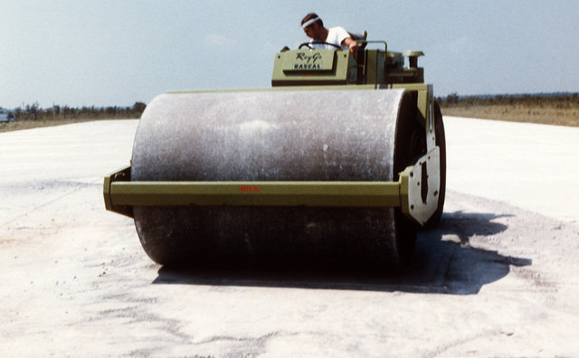 An airman smoothes and levels a patch on a runway, using a steamroller, during a training exercise on rapid runway repair procedures