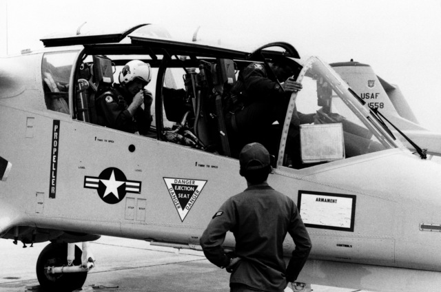 COL John R. Layman, commanding officer, 131st Tactical Fighter Wing, adjusts his headphone set as he sits in the OV-10 Bronco aircraft, and his co-pilot climbs aboard