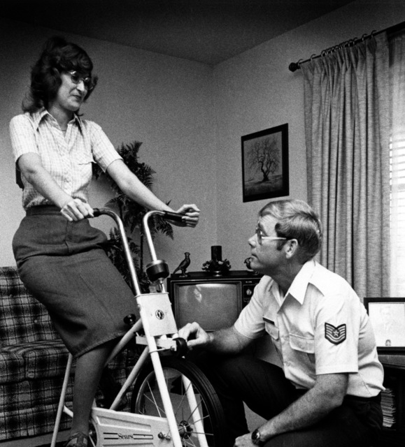 TSGT Bob King adjusts the tension on the exercise bicycle his wife is peddling. Katy King would probably be dead today if she had not had a heart transplant on April 4, 1975