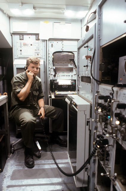 A senior airman talks on a conference line in a complex during a joint tactical information distribution system (JTIDS) training exercise