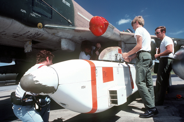 Personnel load a joint tactical information distribution system (JTIDS) pod onto an F-4 Phantom II aircraft during a training exercise