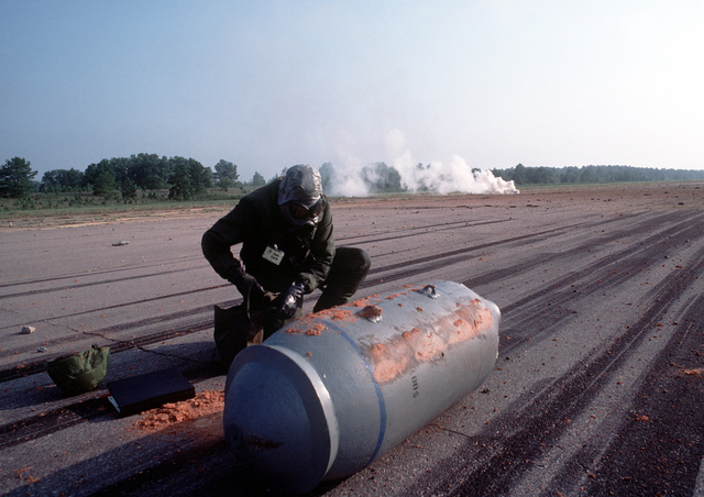 "SSGT Henry Domme checks an ""unexploded"" (inert) bomb during Prime Beef, a simulated runway attack exercise"