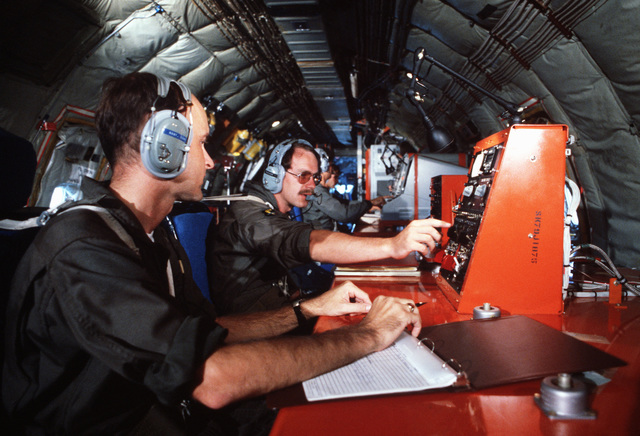 United States Air Force officers monitor radar consoles aboard an NKC-135 Stratotanker aircraft in flight during a joint tactical information distribution system (JTIDS) training exercise