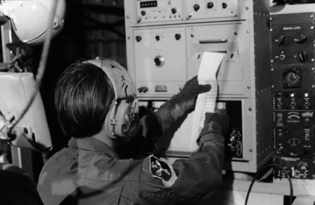 A technician examines an instrument readout aboard a WC-130 Hercules aircraft of the 815th Weather Reconnaissance Squadron, 920th Weather Reconnaissance Group, during an investigation of Hurricane Allen