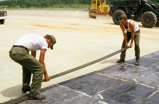 Airmen position metal plates along the edges of a membrane tarp covering a runway crater that is being repaired during a quick reaction runway repair test