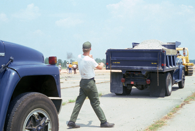 An airman directs trucks carrying gravel that will be used to fill a runway crater is measured and inspected during a quick reaction runway repair test