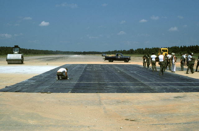 An airman inspects a membrane tarp covering a runway crater being repaired during a quick reaction runway repair test