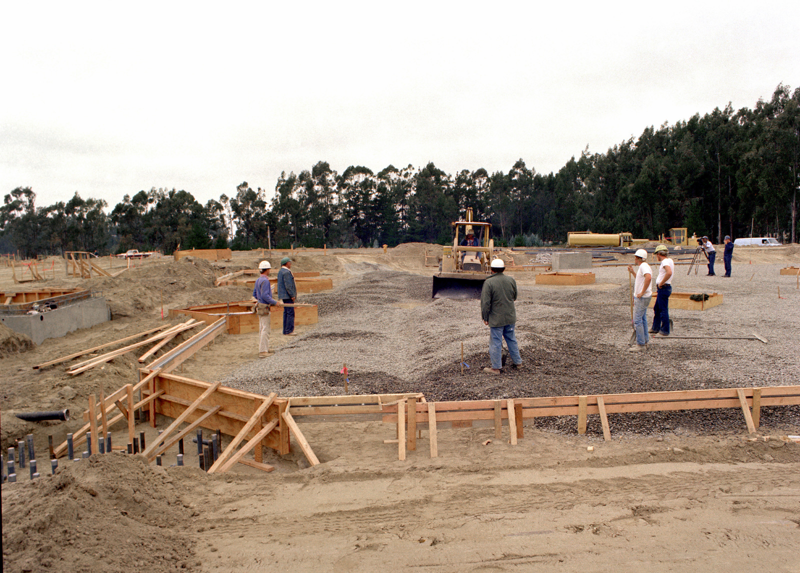 Builders place soil and plastic down as a vapor barrier for the floor of the MX integrated test facility (ITF) during the construction of the MX facilities