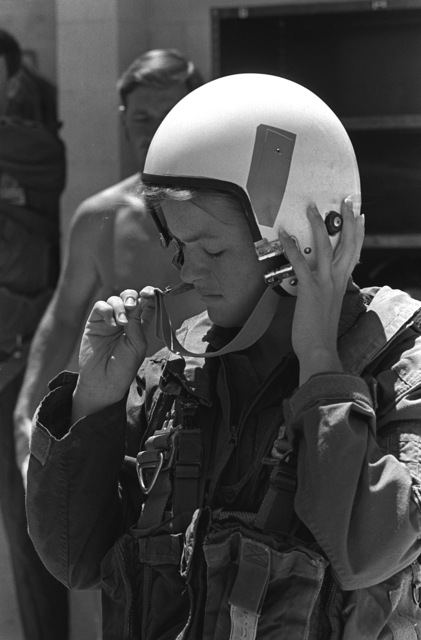 A female midshipman adjusts the chin strap of her flight helmet prior to beginning water survival training at the Aviation Physiology Training Unit pool. The midshipman is participating in a one-week aviation training program for students enrolled in the Naval Reserve Officers Training Corps (NROTC)