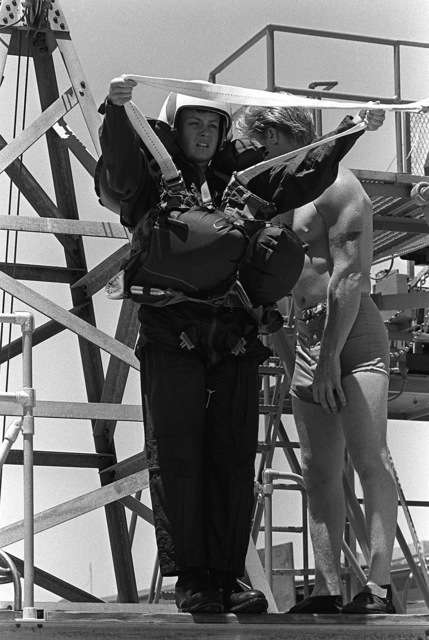 A female midshipman prepares to jump off a platform into the pool during the parachute drag phase of water survival training at the Aviation Physiology Training Unit. The midshipman is attending a one-week training program for students enrolled in the Naval Reserve Officers Training Corps (NROTC)