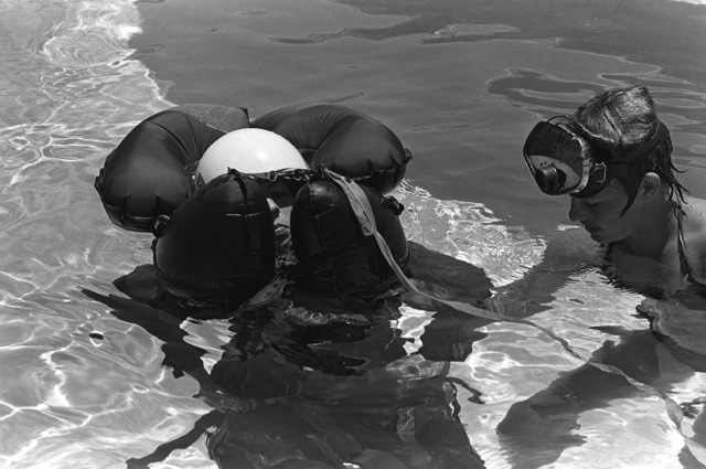 A female midshipman, struggling with her life jacket, is assisted by an instructor during water survival training at the Aviation Physiology Training Unit pool. The midshipman is participating in a one-week aviation training program for students enrolled in the Naval Reserve Officers Training Corps (NROTC)