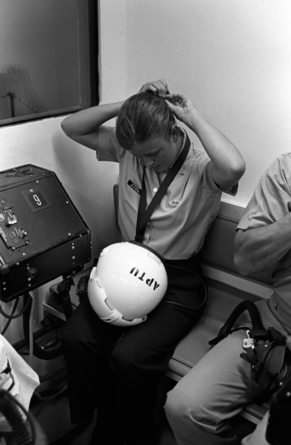 """A female midshipman ties her hair up prior to putting on a flight helmet for her simulated """"flight"""" in a hyperbaric chamber at the Aviation Physiology Training Unit. She is participating in a one-week aviation training program for students enrolled in the Naval Reserve Officers Training Corps (NROTC)"""