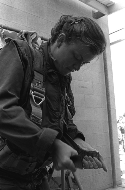 A female midshipman tightens the torso harness of her flight suit prior to the beginning of water survival training at the Aviation Physiology Training Unit. The midshipman is participating in a one-week aviation training program for students enrolled in the Naval Reserve Officers Training Corps (NROTC)