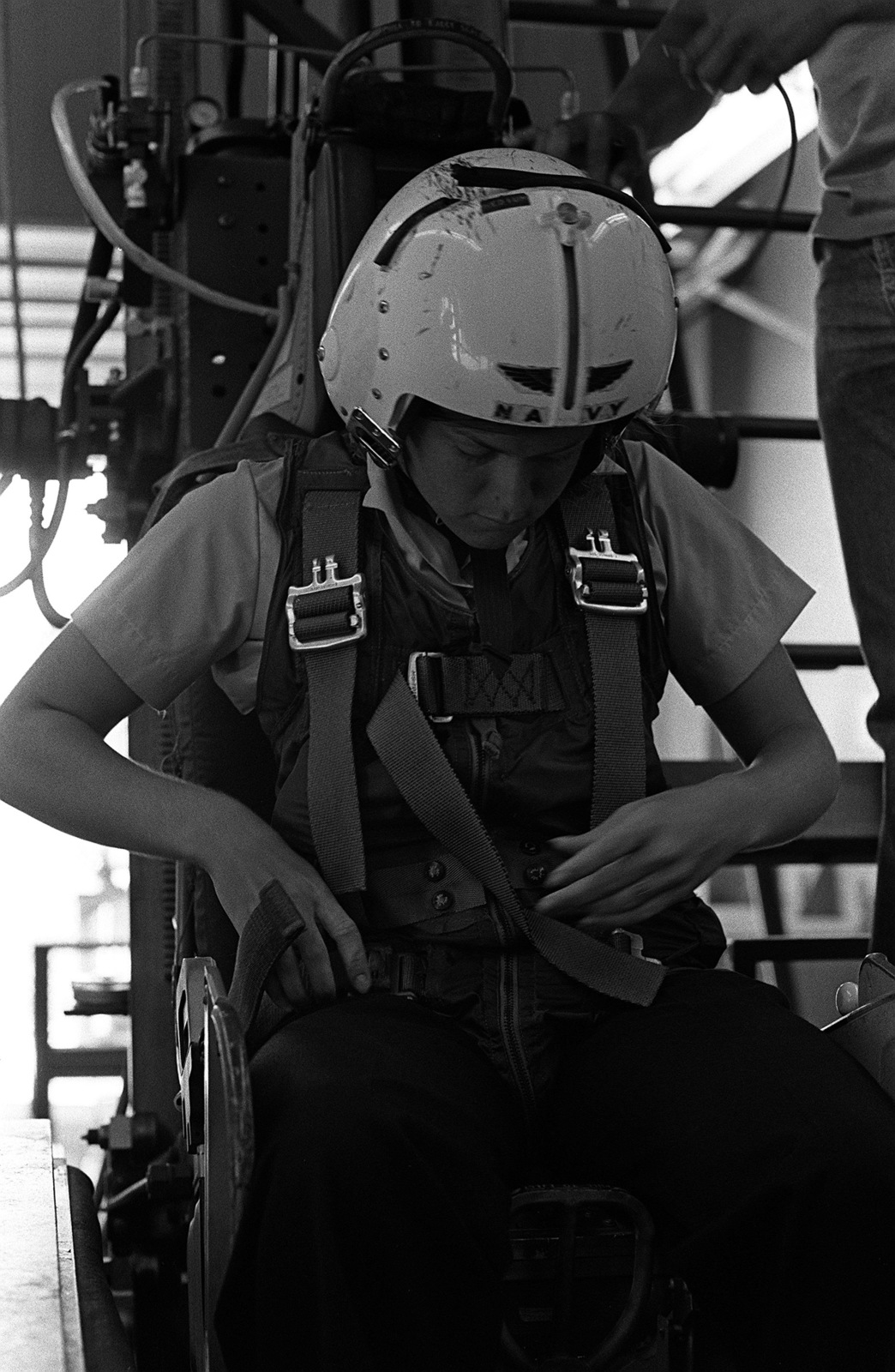 A female midshipman tightens the torso harness on an ejection seat trainer. Ejection seat training is part of a one-week aviation training program for students enrolled in the Naval Reserve Officers Training Corps (NROTC)