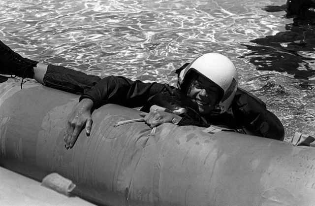A female midshipman, wearing full flight gear, attempts to climb into a life raft during water survival training at the Aviation Physiology Training Unit pool. The midshipman is attending a one-week aviation training program for students enrolled in the Naval Reserve Officers Training Corps (NROTC)