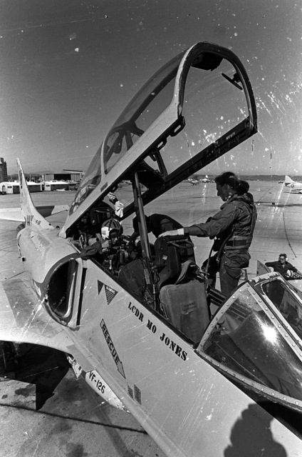 A ground crewman helps Midshipman Cindy Mason buckle herself into the rear seat of a TA-4 Skyhawk aircraft for a demonstration flight. The pilot for the flight is LT. Mary Jorgenson Fighter Squadron 126 (VF-126. Mason is participating in a one-week aviation training program for students enrolled in the Naval Reserve Officers Training Corps (NROTC)