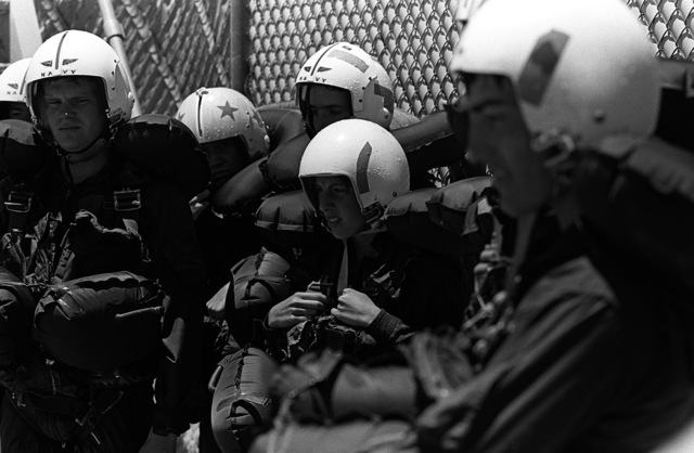 A group of midshipmen listens to final instructions prior to beginning the parachute entanglement phase of water survival training at the Aviation Physiology Training Unit pool. The students are attending a one-week aviation training program for students enrolled in the Naval Reserve Officers Training Corps (NROTC)