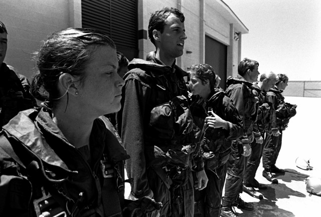 A group of midshipmen watches as other midshipmen undergo water survival training at the Aviation Physiology Training Unit pool. They are participating in a one-week training program for students enrolled in the Naval Reserve Officers Training Corps (NROTC)