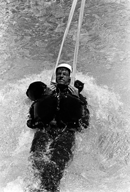 A midshipman is pulled across the surface of the pool by a tow line during the parachute drag phase of water survival training at the Aviation Physiology Training Unit. The midshipman is attending a one-week training program for students enrolled in the Naval Reserve Officers Training Corps (NROTC)