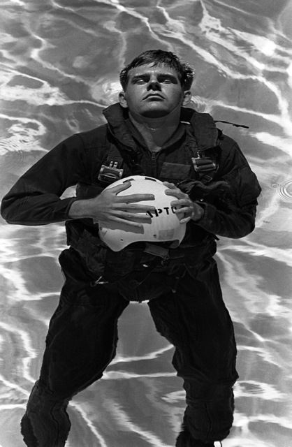 A midshipman uses his foam-lined flight helmet s a flotation device during water survival training at the Aviation Physiology Training Unit. The midshipmen is participating in a one-week aviation training program for students enrolled in the Naval Reserve Officers Training Corps (NROTC)