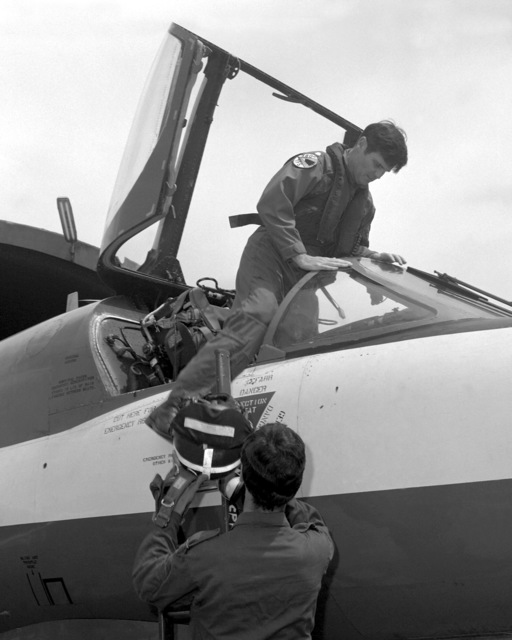 A Royal Air Force pilot helps a U.S. Air Force pilot climb into an aircraft during an RAF visit to the base