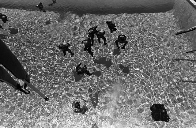 An overhead view of midshipmen undergoing water survival training at the Aviation Physiology Training Unit pool. The midshipmen are participating in a one-week aviation training program for students enrolled in the Naval Reserve Officers Training Corps (NROTC)