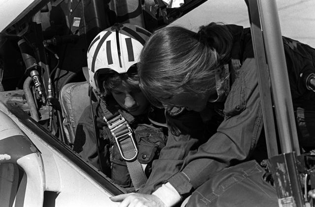 LT. Mary Jorgenson, a pilot with Fighter Squadron 126 (VF-126 points out some of the rear seat cockpit controls to Midshipman Cindy Mason. Mason will take a demonstration ride in the TA-4 during a one-week aviation training program for students enrolled in the Naval Reserve Officers Training Corps (NROTC)