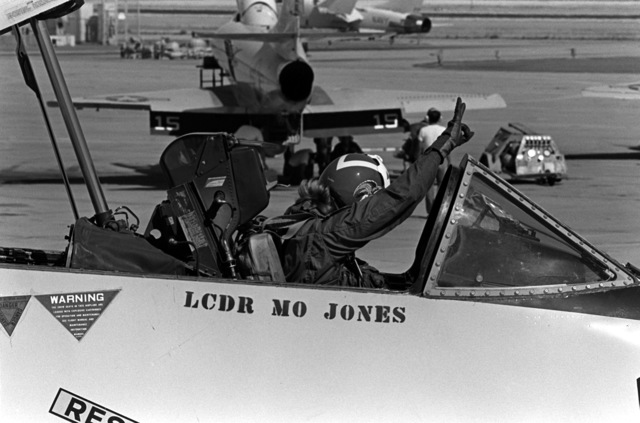LT. Mary Jorgenson, a pilot with Fighter Squadron 126 (VF-126, signals from the cockpit of a TA-4 Skyhawk aircraft that she is ready to begin her flight. LT. Jorgenson is taking a midshipman on a demonstration flight during a one-week aviation training program for students enrolled in the Naval Reserve Officers Training Corps (NROTC)