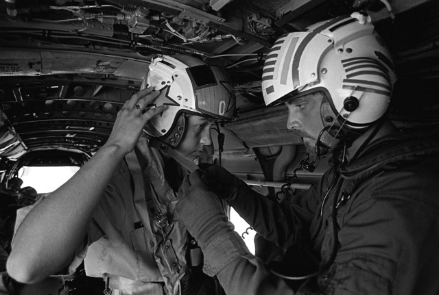 Midshipman 2nd Class Fraley adjusts her flight helmet while an aircrewman from Helicopter Anti-submarine Squadron 8 (HS-8) assists. She is on a demonstration flight in a CH-46 Sea Knight helicopter as part of a one-week aviation training program for students enrolled in the Naval Reserve Officers Training Corps (NROTC)