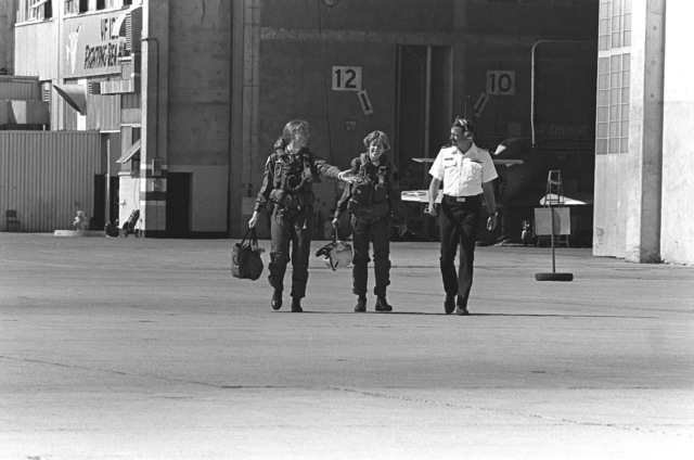 Midshipman Cindy Mason, center, and LT. Mary Jorgenson, a pilot with Fighter Squadron 126 (VF-126), are escorted to the flight line by a public affairs officer. Mason will go on a demonstration in a TA-4 Skyhawk aircraft during a one-week aviation training program for students enrolled in the Naval Reserve Officers Training Corps (NROTC)