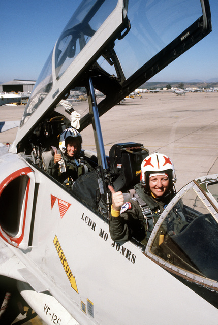 Midshipman Cindy Mason, in the rear, and LT. Mary Jorgenson, a pilot with Fighter Squadron 126 (VF-126, gives the thumbs-up signal prior to taking off on a familiarization flight in a TA-4 Skyhawk aircraft. Mason is participating in a one-week aviation training program for students enrolled in the Naval Reserve Officers Training Corps (NROTC)