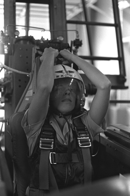 Midshipman, Cindy Mason prepares to pull down the face curtain that will launch the ejection seat up the track of the ejection seat trainer. Ejection seat training is a part of a one-week aviation training program for students enrolled in the Naval Reserve Officers Training Corps (NROTC)