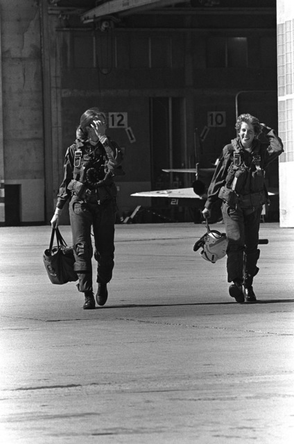 Midshipman Cindy Mason right, and LT. Mary Jorgenson, a pilot with Fighter Squadron 126 (VF-126) walk out to the flight line. Mason will go on a demonstration in a TA-4 Skyhawk aircraft during a one-week aviation training program for students enrolled in the Naval Reserve Officers Training Corps (NROTC)