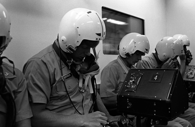 """Midshipman Van Buer adjusts the straps of his oxygen mask prior to his simulated """"flight"""" in a hyperbaric chamber at the Aviation Physiology Training Unit. He is participating in a one-week aviation training program for students enrolled in the Naval Reserve Officers Training Corps (NROTC)"""