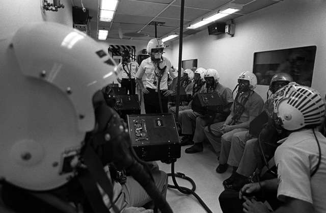 Midshipmen wearing flight helmets and oxygen masks prepare to undergo high-altitude flight testing in a hyperbaric chamber at the Aviation Physiology Training Unit. The midshipmen are participating in a one-week aviation training program for students enrolled in the Naval Reserve Officers Training Corps (NROTC)