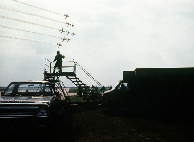 A camera crew from Detachment 3, 1361st Audiovisual Squadron, Rhein-Main Air Base, West Germany, video tapes the Red Arrows Flight Demonstration Team during Air Fete '80. AN Aerospace Audiovisual Service (AAVS) television van, not visible, is used to monitor what is being recorded