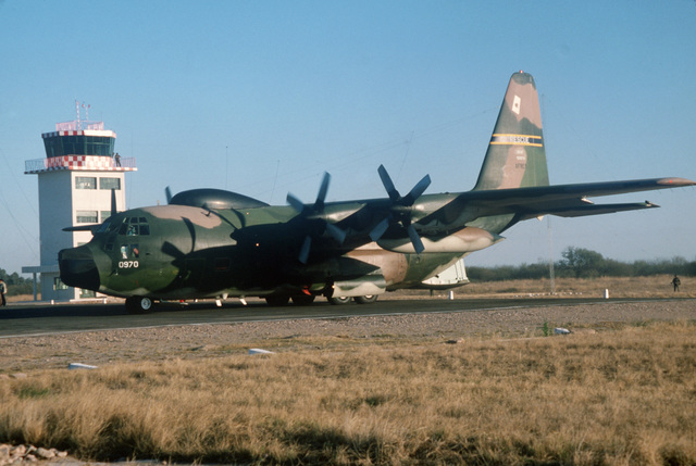 An Air Force Reserve HC-130 Hercules aircraft lands at a remote mountain airfield to deliver personnel and supplies during disaster relief Exercise ATX-80