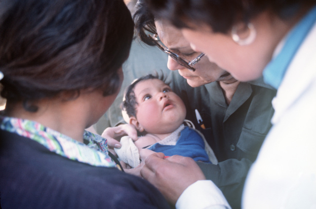 US Air Force medical personnel examine a baby during disaster relief Exercise ATX-80