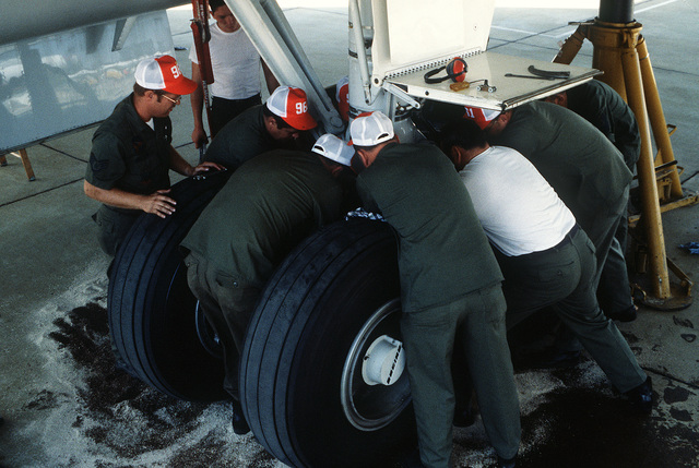 Maintenance crew members change a seal on an E-3A Airborne Warning and Control System aircraft. The crew are members of the 961st Airborne Warning and Control Support Squadron, involved in Exercise Pacific Consort