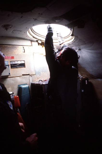 The 7th Special Operations Squadron (SOS) conducts training for special air operations and related activities. The unit also trains with Army Special Forces and Navy SEALS for unconventional warfare operations. A crewman retrieves an upper lift line through an overhead escape hatch of an MC-130E Hercules Combat Talon aircraft during a Fulton recovery