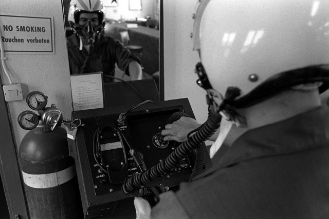 An airman 1ST class uses an MQ-1 tester to test an HGU-2/AP flight helmet and an HBU-5/P oxygen mask. The airman is assigned to the Wild Weasel life support section of the 81st Tactical Fighter Squadron